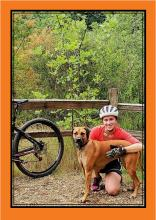 Picture of Jessica Robinson, bike, and Eta (dog).